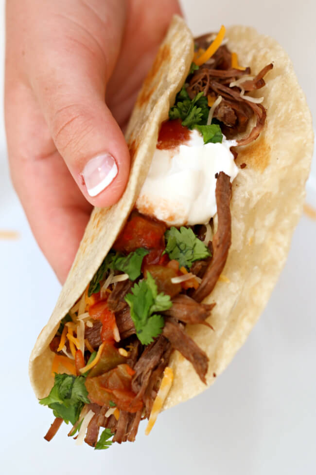 Slow Cooker Beef Barbacoa--flavorful, seasoned beef chuck roast that shreds like a dream and is perfect for so many different dinners. Try this barbacoa beef in cheesy quesadillas, crispy tacos, rolled up as enchiladas or piled on top of nachos.