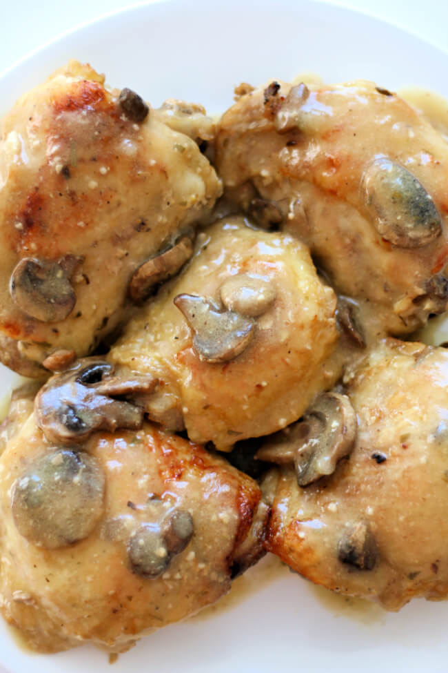 Slow Cooker Dijon Chicken--tender bites of bone-in chicken thighs and mushrooms are covered in a dijon, lemon and tarragon sauce.