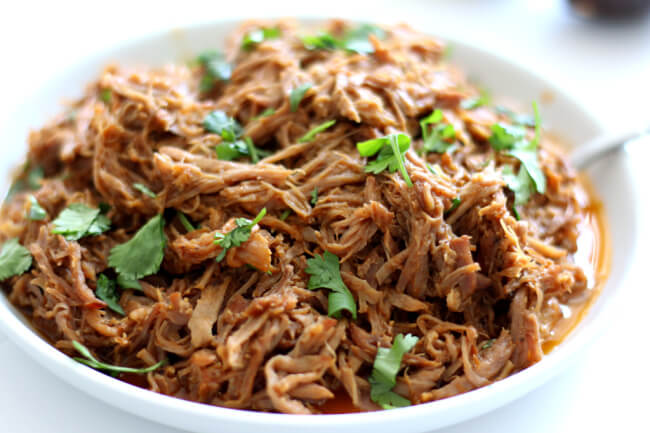 Slow Cooker Cafe Rio Sweet Pork--make your favorite restaurant's sweet pork at home with just a handful of ingredients. This pulled pork is perfect over salad, rice, tacos, burritos, quesadillas or on a toasted bun.