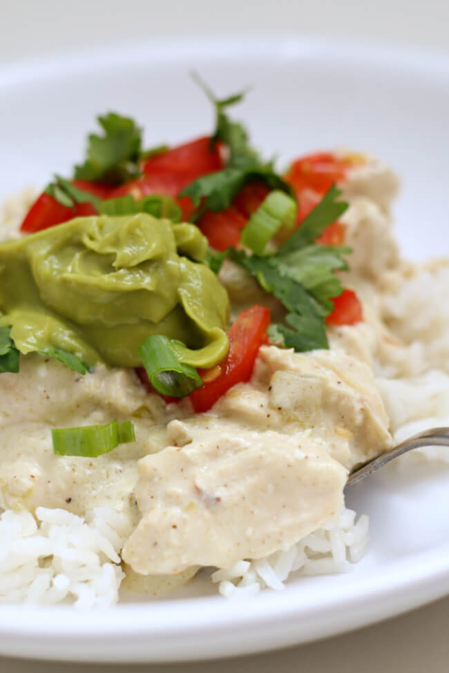 Instant Pot White Chicken Enchilada Bowls--chopped chicken is encompassed in a velvety white sauce made with sour cream, cream cheese and diced green chilies. The sauce is served over rice and topped with colorful toppings. An easy way to enjoy the flavors of enchiladas without a ton of work.