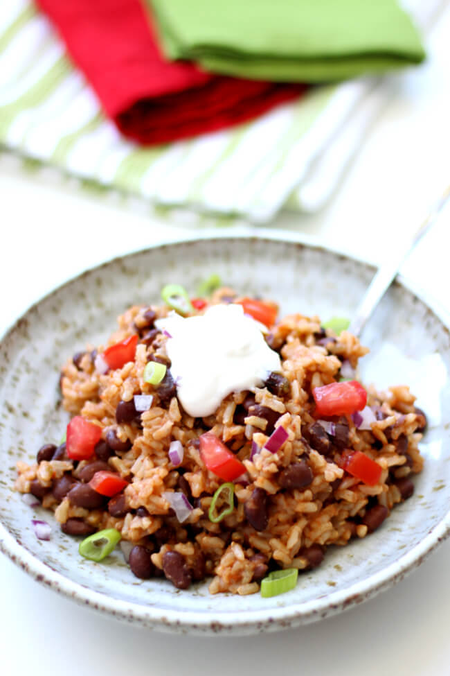 Instant Pot Mexican Black Beans and Rice–the easiest and tastiest rice ever! Brown rice is cooked in flavorful salsa with garlic salt, a bay leaf and cumin. Canned black beans make this recipe very convenient. And my favorite part is a squeeze of lime juice and a dollop of sour cream on top.