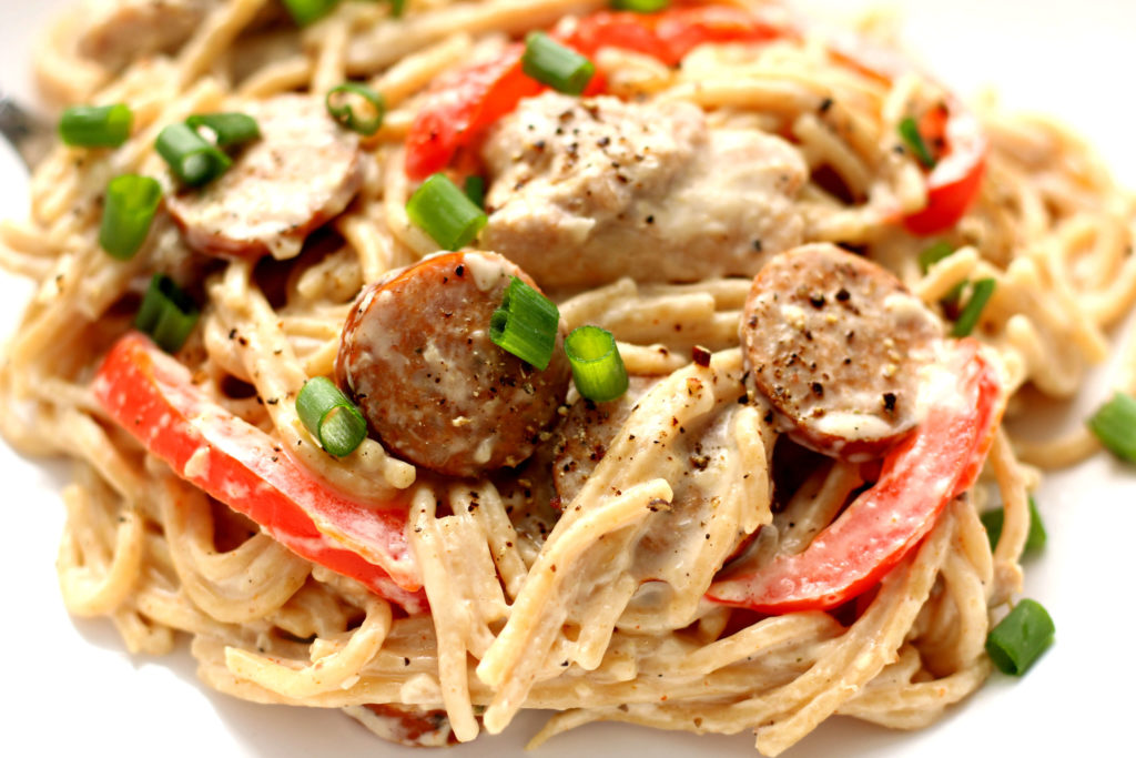 Instant Pot Cajun Chicken Pasta--pasta with chunks of chicken, bites of andouille sausage, bell peppers, creamy sauce and cajun seasoning.