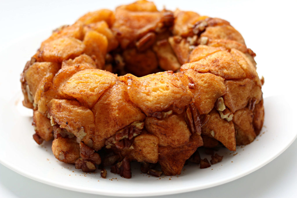 White background with a bundt cake shape of monkey bread on top with chopped pecans