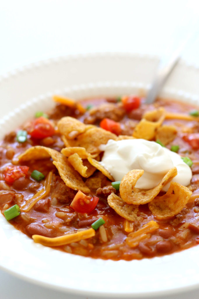 bowl of chili with sour cream and fritos