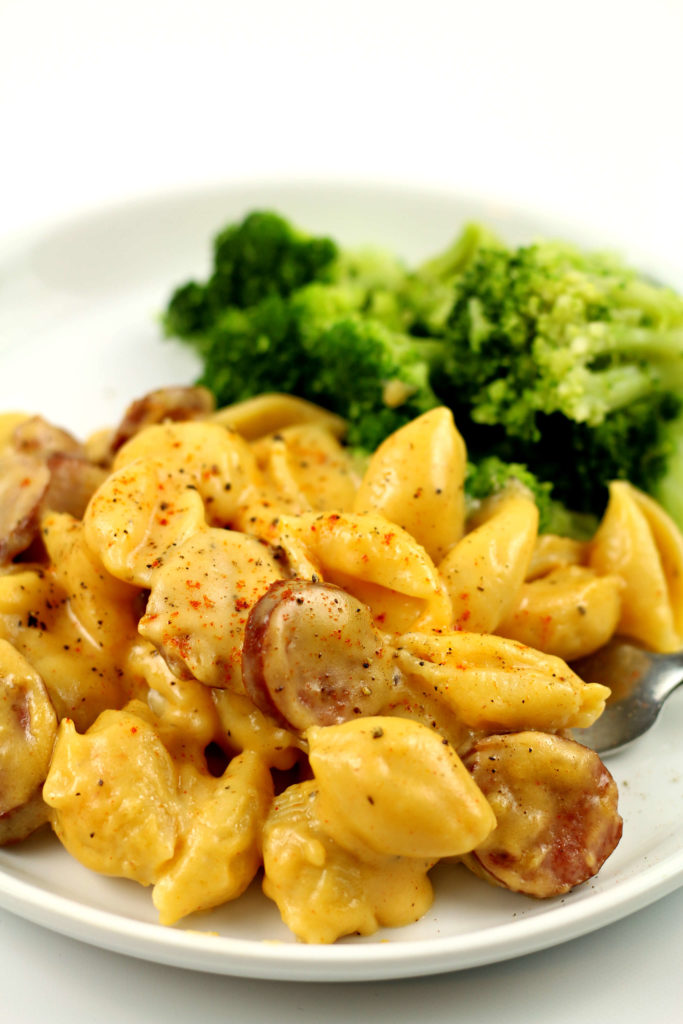 pasta shells on a white plate with broccoli in the background