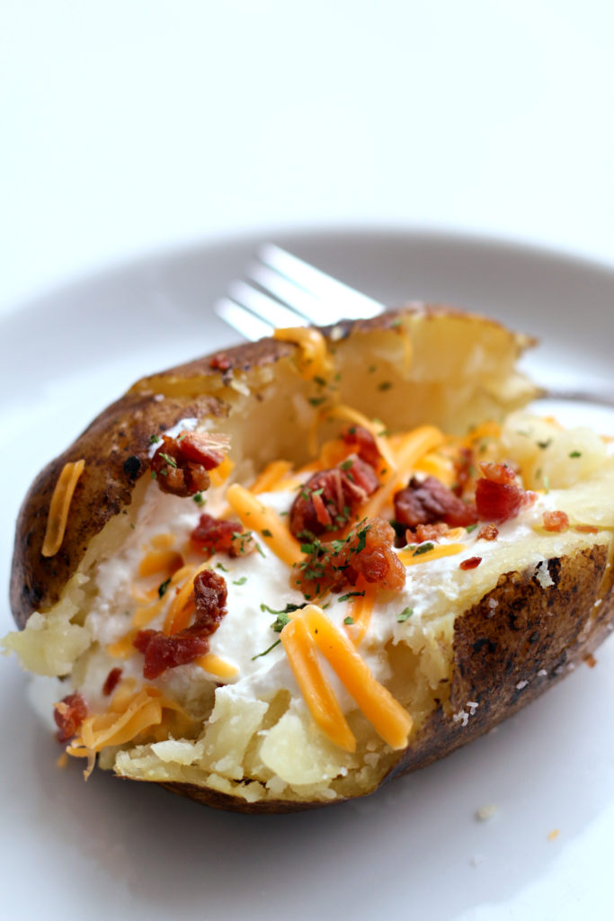 baked potato with cheese, sour cream and bacon on a white plate