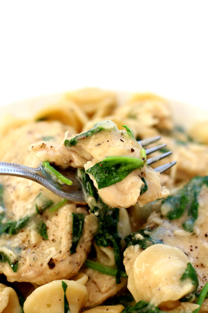 chicken, pasta and spinach on a white plate