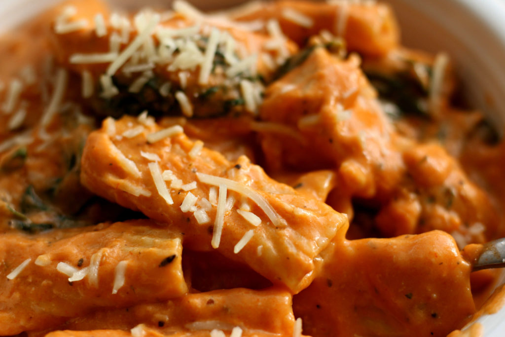white bowl with chicken and pasta with a red cream sauce