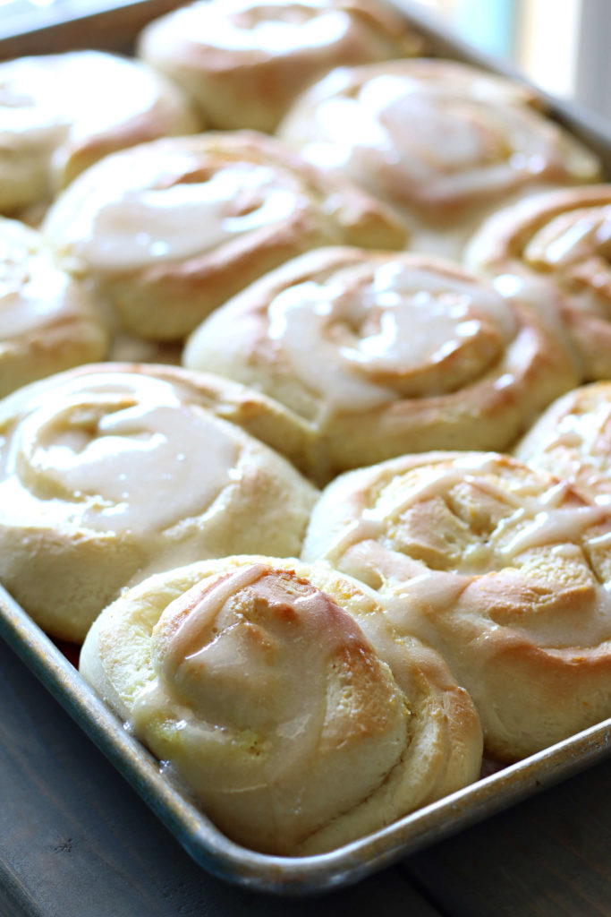 orange rolls on a pan with glaze on top
