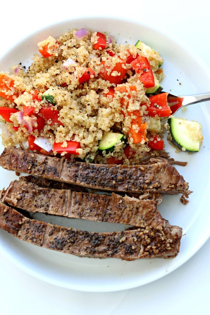 sliced flank steak and quinoa on a plate