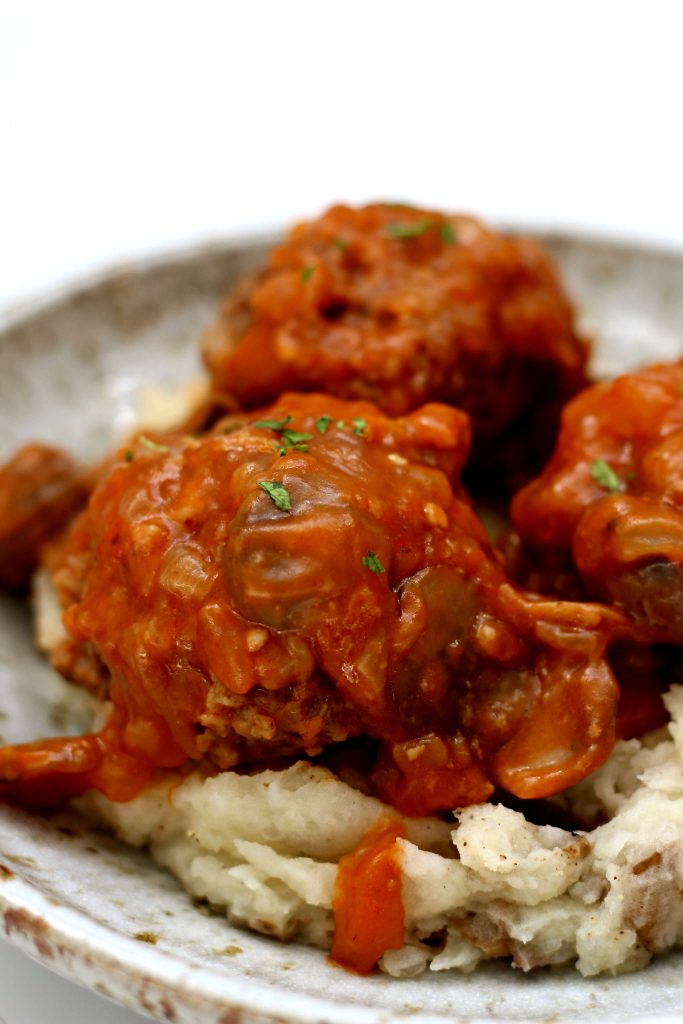 meatballs in a sauce on top of potatoes